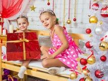 Dziewczyna dać dużemu czerwonemu Bożenarodzeniowemu prezentowi jego siostra i patrzejącemu w ramę Fotografia Stock