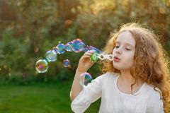 Dziewczyna dmucha mydlanych bąble w lato parku Obrazy Royalty Free
