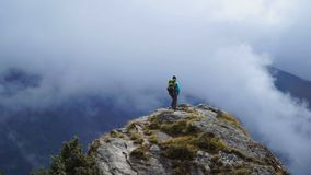 Dziewczyna dosięga w górę wierzchołka góra i podnosić ręki z plecakiem zbiory