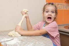 Dziewczyna drzeje daleko kawałek ciasto dla kulebiaków i spojrzenia w ramę szczęśliwie Zdjęcie Stock