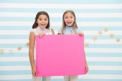 Dziewczyna dzieciaków chwyta reklamy plakata kopii przestrzeń Dziecko chwyta reklamowy sztandar Szczęśliwi dzieci z pustym papier obraz stock