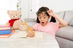 Dziewczyna dzieciaka dzieci pisze ogłoszeniu towarzyskiemu szkolnej pracie domowej zdjęcie royalty free