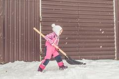 Dziewczyna, dziecko duża łopata usuwa śnieg od ścieżki w podwórko przy garażem zdjęcia royalty free
