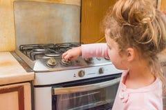 Dziewczyna, dziecko zawiera benzynową kuchenkę pod nieobecność dorosłych, t fotografia stock