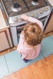 Dziewczyna, dziecko zawiera benzynową kuchenkę pod nieobecność dorosłych, t obraz stock