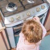 Dziewczyna, dziecko zawiera benzynową kuchenkę pod nieobecność dorosłych, t zdjęcia stock