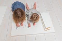 Dziewczyna, dziecko zbiera nowego stół na tle biały bri, obrazy stock