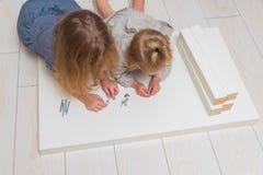 Dziewczyna, dziecko zbiera nowego stół na tle biały bri, fotografia royalty free