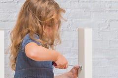 Dziewczyna, dziecko zbiera nowego stół na tle biały bri, fotografia stock