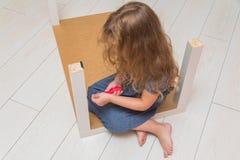 Dziewczyna, dziecko zbiera nowego stół na tle biały bri, zdjęcia royalty free