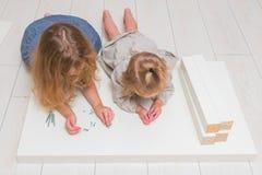 Dziewczyna, dziecko zbiera nowego stół na tle biały bri, zdjęcie stock