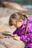Dziewczyna Egzamininuje Plażowego otoczaka zdjęcie royalty free