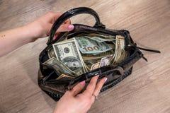 dziewczyna ekstrakta dolary od pakować toreb Fotografia Stock