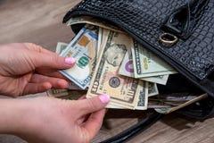 dziewczyna ekstrakta dolary od pakować toreb Obraz Royalty Free