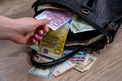 dziewczyna ekstrakta dolary od pakować toreb Obraz Stock