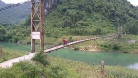 Dziewczyna faceta przejażdżki hulajnoga wzdłuż wąskiego zawieszenie mostu zbiory