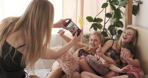 Dziewczyna fotografuje przyjaciół ma zabawę pozuje z imitacji wsparciami na łóżku zbiory