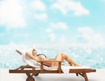 Dziewczyna garbnikuje przy plażą z deckchair zdjęcia stock