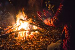 Dziewczyna grże jej ręki od ogienia w noc lesie zdjęcie royalty free