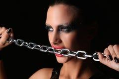 Dziewczyna gryźć łańcuch z bliska Czarny tło Zdjęcie Royalty Free