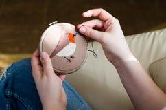 Dziewczyna haftuje ptaka z ściegiem DIY pojęcie, hobby, twórczość, odzież i wewnętrzna dekoracja, zdjęcie stock