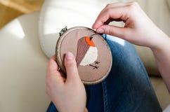 Dziewczyna haftuje ptaka z ściegiem DIY pojęcie, hobby, twórczość, odzież i wewnętrzna dekoracja, zdjęcia stock