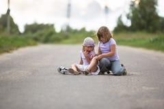 Dziewczyna hulajnoga spadał W wsi, siostra pomaga jej dziecka Fotografia Royalty Free