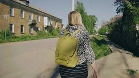 Dziewczyna iść przez zwyczajnego skrzyżowania w kierunku kondygnacja intymnego domu Kamera podąża Wolny playback pogoda jest dobr zbiory wideo