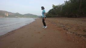 Dziewczyna iść przy jog brykiem wzdłuż plaży przy wschodem słońca zdjęcie wideo