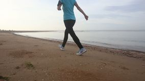 Dziewczyna iść przy jog brykiem wzdłuż plaży przy wschodem słońca zbiory