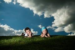 Dziewczyna i chłopiec kłaść na trawie zdjęcia stock