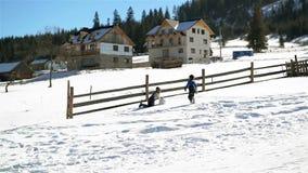Dziewczyna i chłopiec Staczamy się Ogromnego Snowball w górę wzgórza Podczas Ciepłego słonecznego dnia w wsi w górach Dzieci zbiory