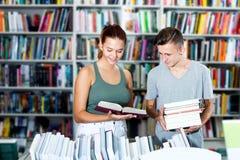 Dziewczyna i chłopiec w książkowym sklepie Zdjęcia Royalty Free