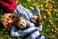 Dziewczyna i dwa chłopiec kłaść na trawie i jemy jabłka obrazy stock