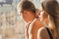 Dziewczyna i facet stoimy obok okno Fotografia Stock