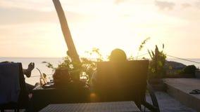 Dziewczyna i faceta obsiadanie w pokładów krzesłach i oglądamy zmierzch tropikalna wyspa zbiory