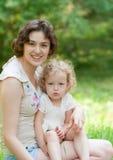 Dziewczyna i jej matka jesteśmy relaksujący w parku Zdjęcie Royalty Free