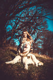 Dziewczyna i jej łuskowaty psi plenerowy w lesie Zdjęcia Stock