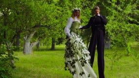 Dziewczyna i mężczyzna na stilts tanczy w parku zbiory