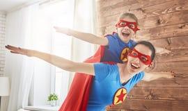 Dziewczyna i mama w bohaterów kostiumach Obrazy Stock