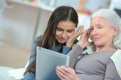 Dziewczyna i piękna babcia używa cyfrową pastylkę obrazy royalty free