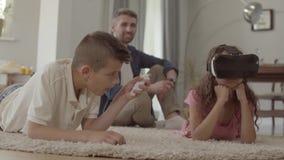 Dziewczyna i używać rzeczywistość wirtualna szkła, ojca obsiadanie na zdjęcie wideo