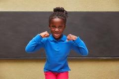 Dziewczyna jako uczeń zaciska jej pięści fotografia royalty free