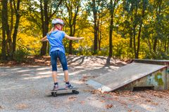 Dziewczyna jeździć na łyżwach w górę rampy na skatepark z longboard fotografia stock