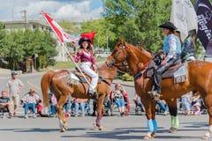 Dziewczyna jeździecki koń i falowanie kanadyjczyk zaznaczamy przy paradą zdjęcia stock