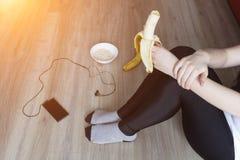 Dziewczyna je banana, owsianka, telefon z hełmofonami, zdrowy styl życia, piękny obrazy royalty free