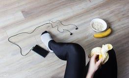 Dziewczyna je banana, owsianki, telefonu z hełmofonami, sera, zdrowego stylu życia, banana i chałupy, obrazy royalty free