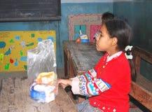 Dziewczyna je jej posiłek przy szkołą w campingowej wycieczce w Egipt Zdjęcia Stock
