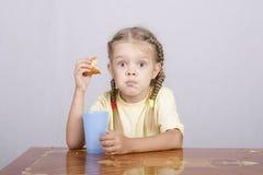 Dziewczyna je słodka bułeczka z sokiem przy stołem Obrazy Royalty Free