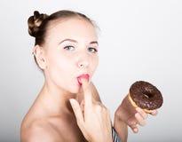 Dziewczyna je smakowitego pączek z lodowaceniem w jaskrawym makeup Śmieszna radosna kobieta z cukierkami, deser około tło bow pus Fotografia Royalty Free